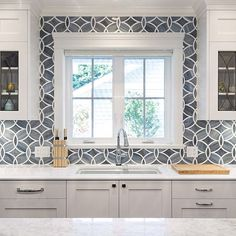A beautiful kitchen with a stunning backsplash designed by @sarahgallopdesign.
