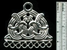 In the Viking Age, chain spreaders / bead hangers / chatelaines were worn in pairs, hung below oval or round brooches. They were used to display strings of colored glass beads and other treasured charms and ornaments. Small tools could be hung from them such as scissors, tweezers or needle cases. This may also be worn singly when used as a chatelaine to carry favorite tools and amulets, hung below a brooch or dangling from a separate chain. They came in many styles from practical a...