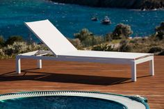 Bright white lounger next to sparkling blue water-Summer is here