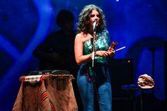 Céu cantora brasileira no show, muito estilosa vestida dr calça jeans, blusa verde brilhosa e cabelo cacheado.