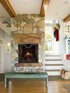 Give your new fireplace a kick of green and some historical character by using salvaged materials. Reclaimed wood makes for a perfect mantel atop aged stone, and an antique bench adds character./