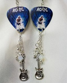 AC/DC Ballbreaker Guitar Pick Earrings with Swarovski Crystal and Charm Dangles  ||  These earrings are made from guitar picks featuring artwork from the album cover of Ballbreaker by AC/DC. I dangled two 6mm Swarovski crystals - one opal and one clear - as well as a metal guitar charm from each earring.They are 4.25 inches long from the top of of the ear wire curve to the very bottom…