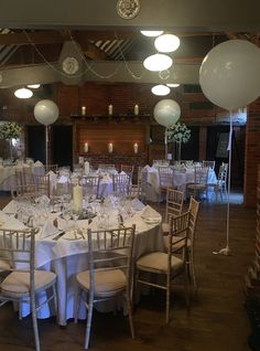 Giant white balloons with white satin tails for a white wedding in the Dawley Barn at swish Hampshire hotel Lainston House