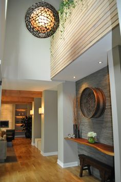 This two-story foyer features a volcanic stone clad wall which serves as a backdrop to a live edge walnut shelf. Above, the planter is finished with the home's original tongue-and-groove wood that once was on the ceiling.