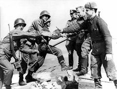 Russian and American soldiers shaking hands and greeting each other as Allies at the end of World War 2. Germany 1945
