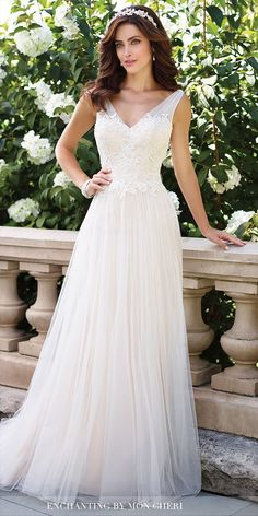 Sleeveless soft tulle and lace A-line gown with gathered illusion straps, front and back low V-necklines, sweetheart lace bodice, gathered full skirt with chapel train.