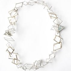 Intertwined Space Necklace £2600.00 This elaborate necklace is inspired by the distorted reflections and negative space found in modern urban environments and industrial architecture. Individually handmade, the simple, geometric elements which make up this piece, combine to present a bold, statement necklace. Constructed from fine square wires of silver and 9ct gold, the piece maintains a delicateness and lightness of form, making it extremely wearable. The way in which the forms are linked…