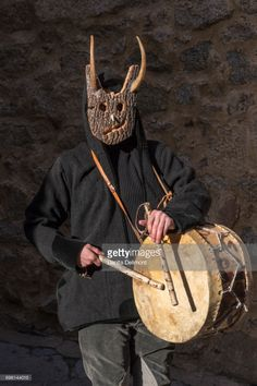 Man in mask playing drums during traditional pagan celebration, Gavoi, Sardinia, Italy