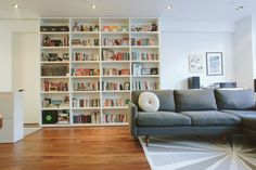 Houzz Tour: Clever Storage Ideas From a Manhattan Duplex -- a floor-to-ceiling bookcase on tracks saves space in the living room by sliding out of the way when not in use.