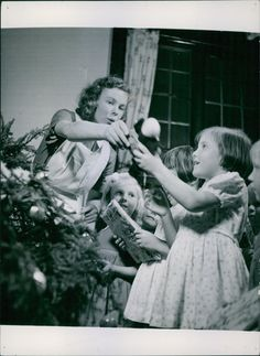 Little girls receiving gifts from the Christmas tree. There is only one copy of each so each image is totally unique.