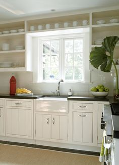 Sweet kitchen design with beadboard ceiling, open white kitchen cabinets with black granite countertops, farmhouse sink, glossy white subway tiles backsplash and jute rug.