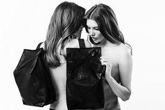 women whispering about handbag smuggle