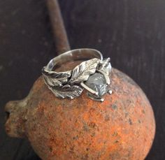 14k white gold engagement ring with a canopy of little leaves surrounding a rough diamond crystal. By Phbeads.com   #raw #rough #diamond #ring #rustic #nature #leaf ring #leaf jewelry #nature inspired #engagement ring
