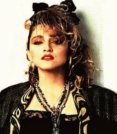 "In the 1980s, rising pop star Madonna proved to be very influential to female fashions. She first emerged on the dance music scene with her ""street urchin"" look consisting of short skirts worn over leggings, necklaces, rubber bracelets, fishnet gloves, hairbows, long layered strings of beads, bleached, untidy hair with dark roots, head bands, and lace ribbons."