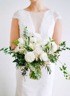 White wedding bouquet by La Fleuriste w Ranunculus, Hellebores, Privet berries, Clematis vines, spray roses, Lily of the Valley, Juniper, & Amaryllis!