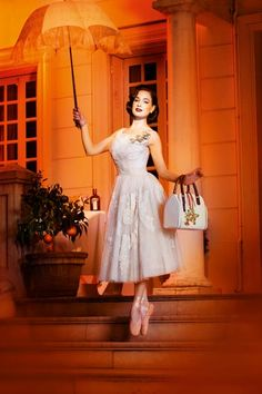 fig.: Dita Von Teese hovering in Mary Poppins style in front of a house. She wears a sleeveless white lace cocktail dress and light-amber colored ballerinas decorated with crystals. In one hand she holds a romantic early 20th century umbrella, in the other the white Cointreau vintage handbag with orange fruit print and two amber colored leather straps. Photographer of the image is Ali Mahdavi for 'My Cointreau Evening by Dita Von Teese'.