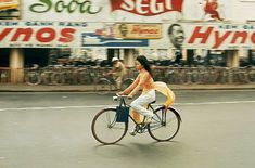 1960's in Saigon, Vietnam, Cyclist in front of the Main Train Station and Ben-Thanh Market. (Photographer: Wilburg) Cuộc sống người Sài Gòn những năm 60 - Một cô gái buộc tà áo dài vào chỗ ngồi sau xe để tránh vướng khi chạy xe đạp. Dọc hai bên đường lúc này là bảng hiệu quảng cáo của thương hiệu kem đánh răng phổ biến thời bấy giờ.