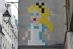 "After a smiley version of Napoleon a couple days ago, Invader is once again back on the streets of Paris with a brand new pixelated design. The anonymous French artist created this large-scale rendering of Alice In Wonderland using mosaic tiles, a design which is now known as ""PA_1170""."