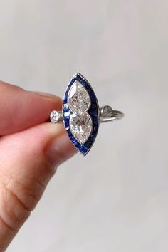 This Art Deco ring sits north to south on the finger. Set with two pear-shaped diamonds each weighing approximately 0.70 carats with EGL certificate stating H - I color and VS2/SI1 clarity, within a calibre-cut sapphire frame with old European-cut diamond accents. Set in platinum. Circa 1920