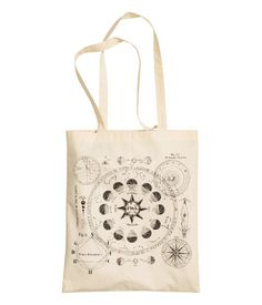 White. Tote bag in woven cotton fabric with a printed motif. Two handles at top. Size 13 3/4 x 16 1/2 in.