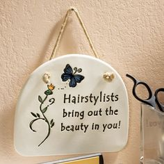 """Hairstylists Bring Out the Beauty Wall Plaque.      Credit Where Credit Is Due. You may provide the raw materials, but your stylist makes the magic happen, making the beauty on the inside show on the outside. Remind that special person that you appreciate them. Hanging sign decorated with flowers reads """"Hairstylists bring out the beauty in you."""""""