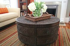 Check out this African Drum Shape Chest. This is a great alternative for a coffee table because of it's curved shape, traditional carvings, and dark organic  wood coloring. This table adds texture and assist with softening up the lines in the room for balance.
