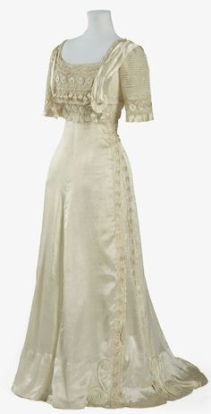 "~Evening Dress: ca. 1905-1909, silk satin. ""This dress epitomises the elegant feminine fashions of the well-to-do in the Edwardian period, particularly in its use of soft flowing pale silk, extensive use of lace and net, and in the ornate decoration of the bodice.""~"