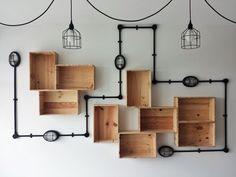 Caixotes de madeira na composição de nichos e lâmpadas na parede.