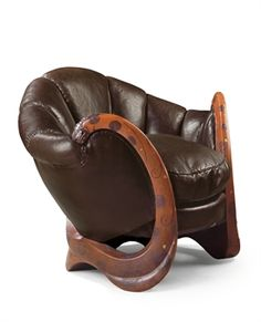 EILEEN GRAY (1878-1976)  FAUTEUIL AUX DRAGONS, VERS 1917-1919 THE 'DRAGONS' ARMCHAIR, CIRCA 1917-1919   In the form of unfurling petals, upholstered in brown leather, the frame in sculpted wood, lacquered brownish orange and silver and modelled as the serpentine, intertwined bodies of two dragons, their eyes in black lacquer on a white ground, their bodies decorated in low relief with stylised clouds $28,238,277.00