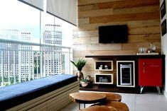 Varanda gourmet com acabamento de madeira na parede.