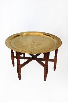 A modern twist on a classic Moroccan brass plate table. This is a two-piece set of the hand-etched brass plate and also a solid wood stand. #homedecor #furniture #table #moroccan #brass
