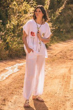 Blusa de silueta holgada en lino, manga corta, cuello redondo y detalle floral bordado con detalles perlados.