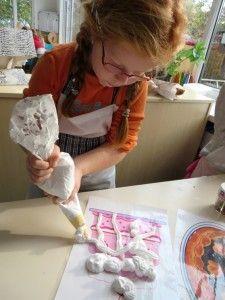 Scheerschuim spuiten op een gelamineerd taart, kleuteridee.nl, thema bakker voor kleuters
