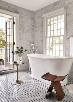 White Tub in Marble Bathroom with Brown Chair
