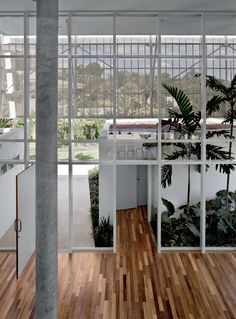 Separados 6,25 m num sentido e 7,50 m no outro, os pilares de concreto apoiam a laje a 6,90 m de altura. Com reforço interno e vidro temperado, as esquarias de alumínio vão do piso ao teto.