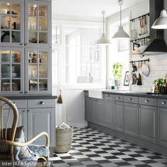Die graue Einbauküche lässt den romantischen Landhausstil cool wirken. Zusammen mit den schwarz-weißen Fliesen ist die Küchengestaltung klassisch und …