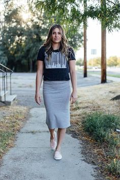 This heather grey pencil skirt is fitted, goes to the knees, and does not include slits. 89% Polyester, 9% Rayon, 2% Spandex.