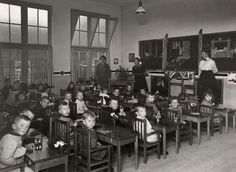Kleutertehuis in Schiedam. In een klaslokaal zitten kleuters elk op een stoeltje met leuningen achter tafels die in rechte rijen staan. De drie kleuterjuffen staan vooraan in het lokaal. Op het bord zijn tekeningen gemaakt. De kinderen kijken vol verbazing naar de fotograaf. Schiedam, Nederland, 1921.