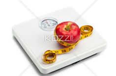 apple tied with tape measure on weight scale. - Close-up shot of an apple tied with measuring tape on weight scale.