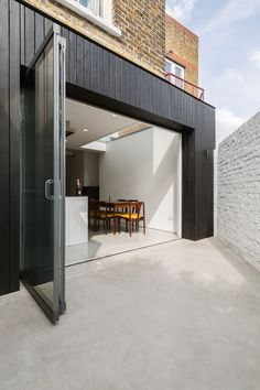 Dickson Architects have revamped a Victorian house in the Arlington Square Conservation area in Islington, North London. The scheme involved extending the rear closet wing to form a full width ground floor extension, providing a large open plan kitchen dining space. Extension is clad in Shou Sugi Ban black charred timber boards. The charred texture of the cladding was chosen to complement the traditional London Stock brick on the rear facade.  Photos by Radu Palicica…