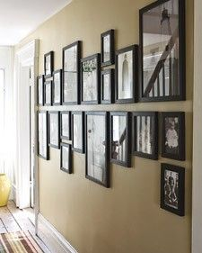 Gallery wall with monochromatic frames aligned either above or below a central, horizontal line (serving as an invisible boundary).