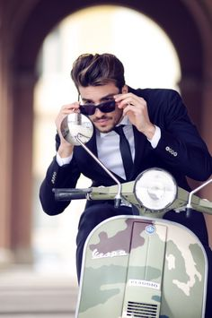 Vespa  Figo....the look is casual but correct enough for biz. Blue suit, skinny tie, nice sun glasses, white shirt. And the Vespa? It's camo.