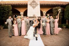 Bridal Party is cheering on the Bride and Groom as they kiss in front of the fireplace | villasiena.cc
