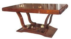 """This French art deco dining table is from the 1930's. Constructed of solid mahogany and mahogany veneers, the table features two pairs of sinuous """"S"""" supports rising from a stepped base with lap feet."""