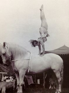 The trick Phryne has to learn to do while the horse is cantering around the ring.  This is the famous May Wirth 1926.