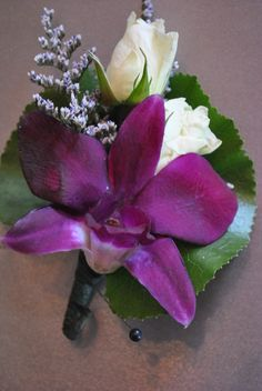 Spray roses, purple orchid, filler and galax leaf.