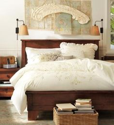 An all-white bed never goes out of style. Accented with a taupe pillow, this bed unifies the neutral tones and works year-round. Natural, linen-shaded sconces soften the light. And a vintage wall display adds impact, plus a touch of warmth to an otherwise blank canvas.  Benjamin Moore™ Paint Color:  OC-67 Ice Mist
