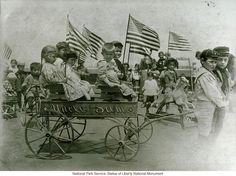 "Immigrant children on ""roof garden"" playground at Ellis Island, with ""Uncle Sam"" cart (Photograph by Augustus Sherman)"
