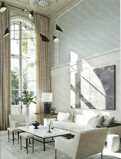 double-height living room with arched windows. Contemporary and formal space (AD)