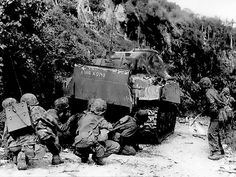 Marines take cover behind one of their medium tanks while cleaning out the northern north end of the island of Saipan on July 8, 1944. The Japanese were well dug in and making their last stand. (Photo: National Park Service)